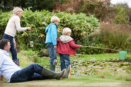 池塘边的家庭休闲生活图片