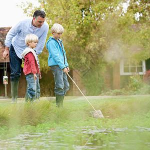池塘边玩耍的父子图片