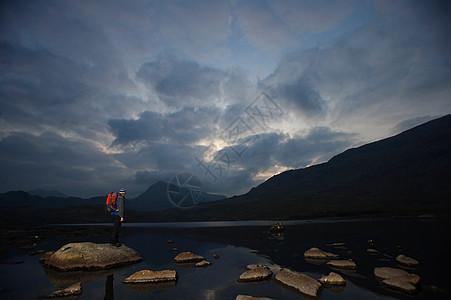 站在湖中岩石上的徒步旅行者图片