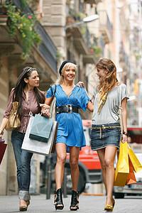 带着购物袋走路的年轻女性们图片