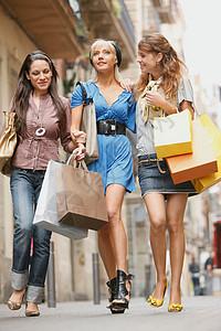 带着购物袋走路的年轻女性图片