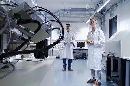 两名穿着实验室外套和安全眼镜的科学家站在实验室里图片