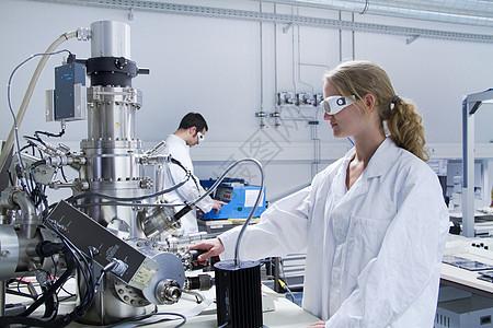 两名科学家穿着实验室外套使用科学设备图片