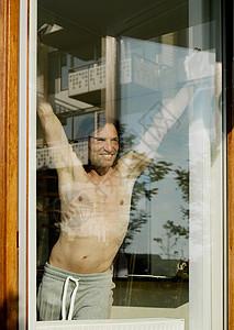 赤裸上身的男人站在窗口图片