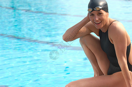 女游泳运动员坐在池边微笑图片
