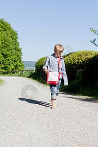 男孩赤脚在乡村公路上行走图片