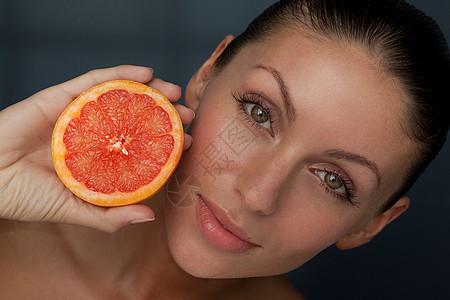拿着一半葡萄柚的女人图片