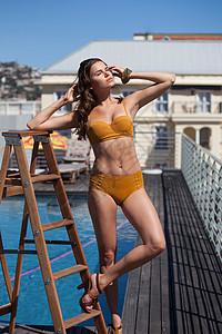 游泳池边穿比基尼的女人图片