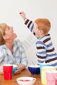母亲和儿子在桌子上玩耍图片
