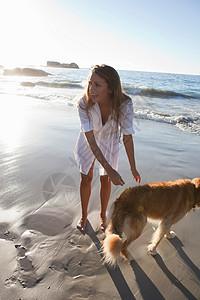 女人在海滩上遛狗图片