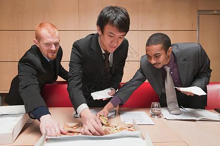 三个年轻商人拿三明治图片