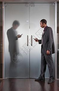 两个商人在手机上发短信图片