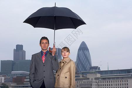 带雨伞城市景观的男人和女人图片