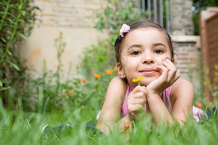 女孩趴在草地上图片