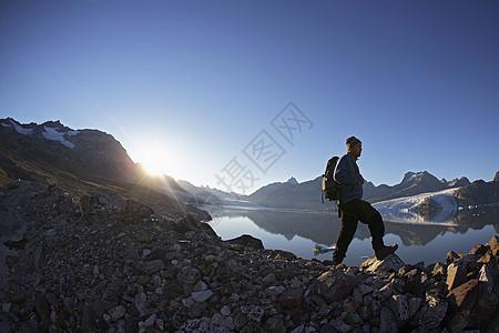 徒步旅行者沿着岩壁行走图片