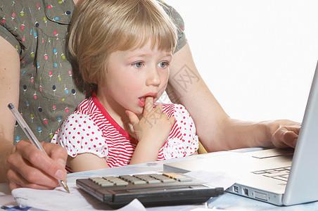 坐在母亲膝上看电脑的女孩图片