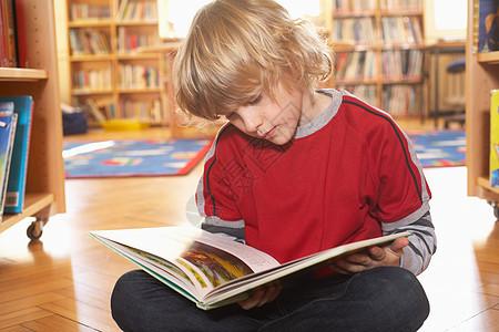 男孩在地板上看书图片