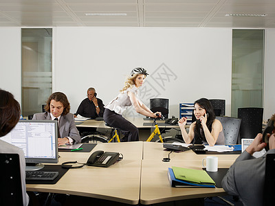 一个女孩在办公室里骑自行车图片
