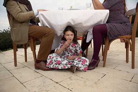 在桌子下面吃蛋糕的女孩图片