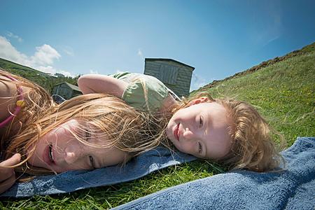女孩们躺在草地上的毛巾上图片