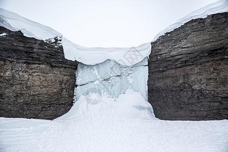 挪威斯瓦尔巴岩石间的冰冻瀑布景观图片