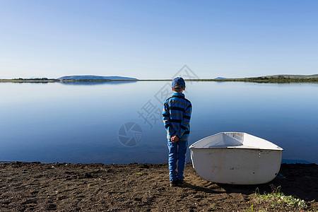 站在湖边划艇旁边的小男孩图片