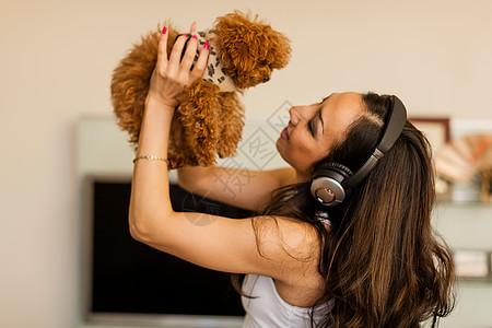 戴着耳机和与狗共舞的中年妇女图片