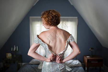 卧室里的女人解开晚礼服上的拉链图片