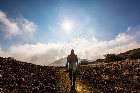 在阳光明媚的风景中拿着相机的中年男子图片