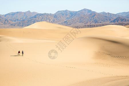 两个人走过美国加利福尼亚州死亡谷的沙地图片