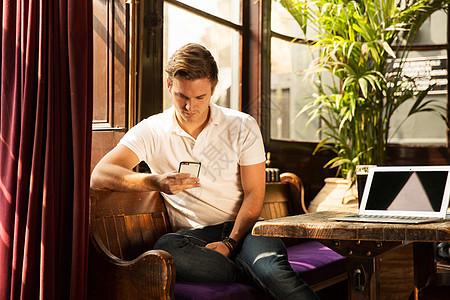 坐着看智能手机的年轻人图片