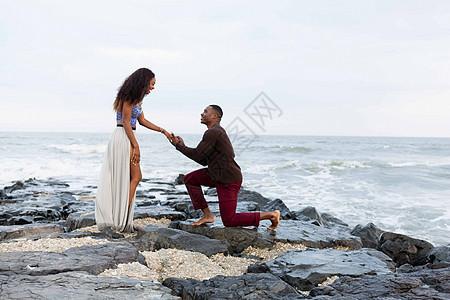 男子跪在海边的岩石上求婚图片