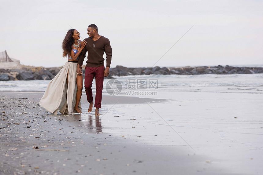 一对夫妇沿着海滩散步图片