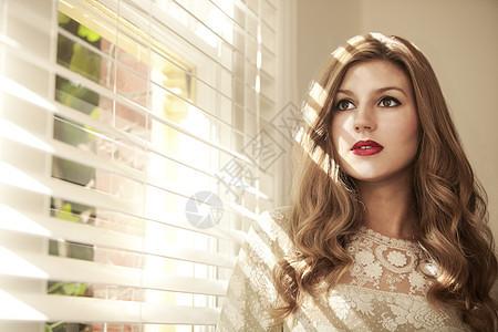 美女透过百叶窗凝视窗外图片