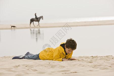 小男孩躺在沙滩上图片