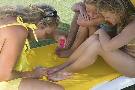 母亲在画两个女孩的脚趾甲图片