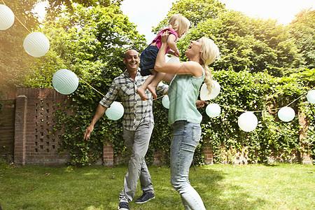 快乐的一对在花园里和蹒跚学步的女儿玩耍图片
