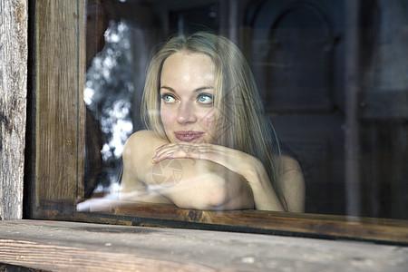 透过窗户看向外面的女孩图片