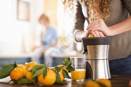 小女孩在厨房里榨橘子汁图片