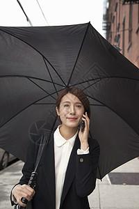 带伞的女商人,在街上用智能手机图片