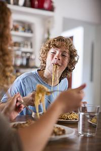 十几岁的男孩在餐桌上吃意大利面图片