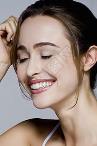 闭着眼睛微笑的年轻女子的摄影棚肖像图片