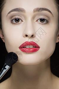 剪短的工作室拍摄的宁静的年轻女子和化妆刷图片