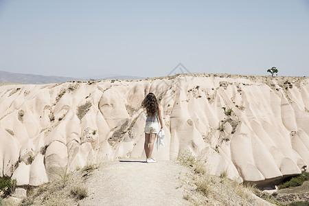 土耳其,安纳托利亚,卡帕多西亚,从岩石中眺望的女性游客的后视图图片