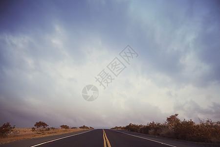 美国夏威夷科纳区笔直空旷的公路和风暴云图片