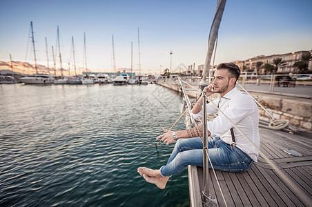意大利撒丁岛卡利亚里游艇上使用智能手机的年轻人图片