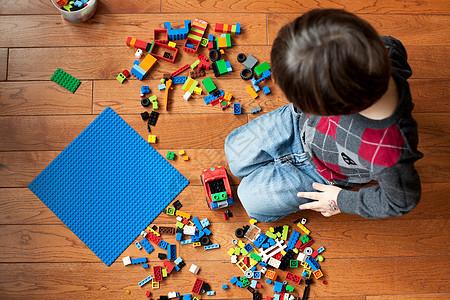 男孩在地板上玩玩具块图片