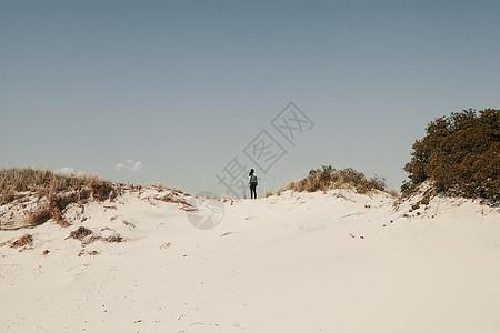 中年妇女站在美国纽约州琼斯海滩沙丘上图片