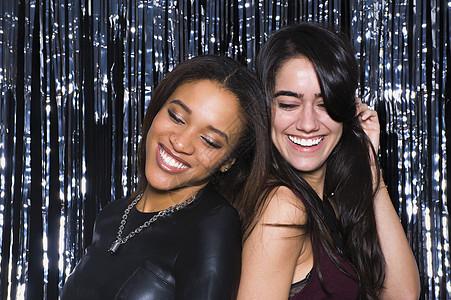 在夜总会里两个年轻女子背靠背地跳舞图片