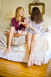 两位年轻女性朋友在涂指甲油时坐在床上大笑图片